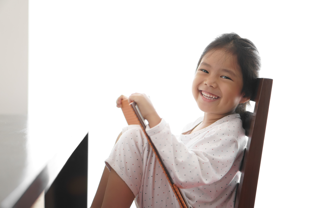 young-girl-smiling-while-sitting-on-a-chair