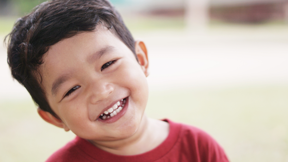 a kid smiling after a consultation on gum disease